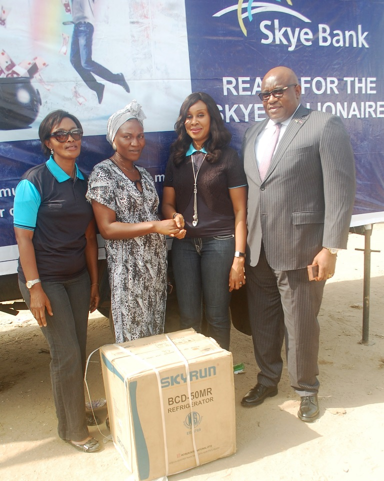 "L-R: Area Manager, Greater Lagos 2, Skye Bank Plc., Adejumoke Odutola, Winner of one of the instant giveaway prizes, Muibat Adelana, Head, Retail Banking, Skye Bank Plc., Nkolika Okoli and Regional Director, Ikeja, Skye Bank Plc., Ndubuisi Osakwe at the Bank's ""Reach For The Skye"" reward draw held in Better Life Main Market, Ikorodu area of Lagos on Thursday"